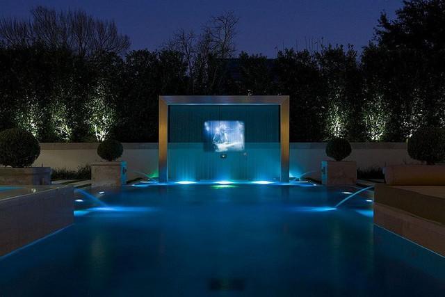 Hồ bơi hiện đại kết hợp với vòi phun nước và màn hình chiếu sáng vào ban đêm cực quyến rũ.