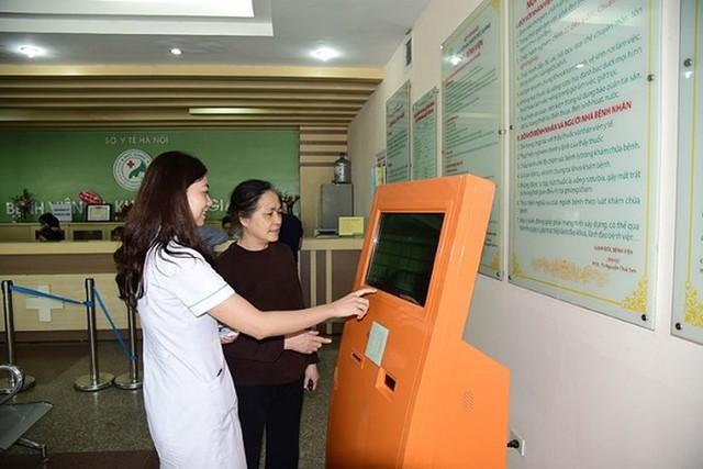 Nhân viên y tế Bệnh viện Đức Giang hướng dẫn bệnh nhân đặt thẻ thông minh vào máy đăng ký khám tự động. Ảnh: TL
