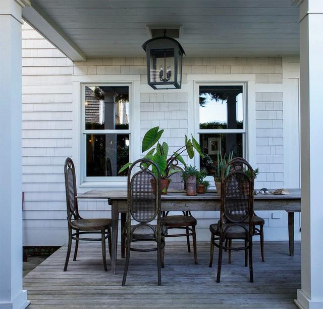 Một phần hiên nhà được đặt bộ bàn ăn kiểu dáng Vintage với màu thô mộc của gỗ. Không gian như dịu dàng và ấn tượng hơn khi có điểm xuyết từ sắc xanh của những chậu cây trang trí.