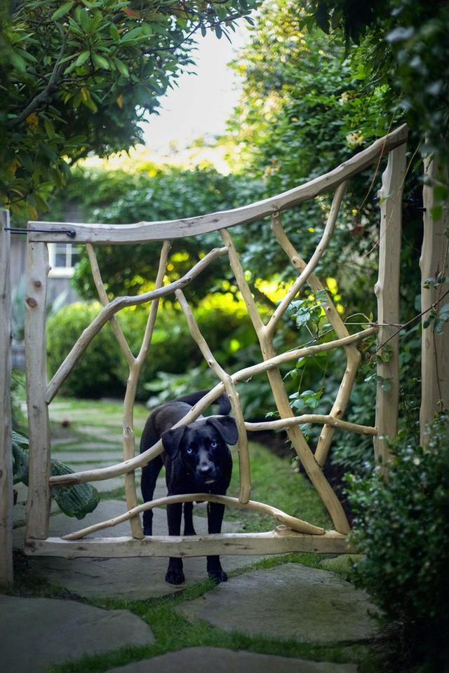 Lối vào từ cổng phụ cũng được thiết kế xinh xắn với gỗ từ thân cây đan xen nhau vô cùng tinh tế.