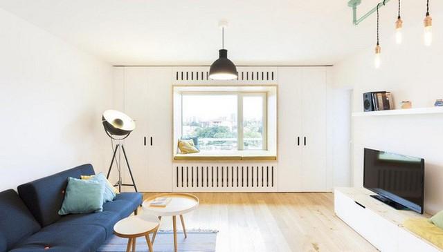 Góc phòng khách được chọn ghế sofa êm ái, đơn giản và nhỏ gọn. Không gian màu trắng tinh của tường và trần trở thành gam nền giúp màu xanh hải quân của sofa và bàn trà màu gỗ thêm nổi bật. Phía đối diện được bố trí thêm góc ngồi xinh xắn cùng hệ thống kệ treo, ti vi để tăng thêm tiện ích khi sử dụng.