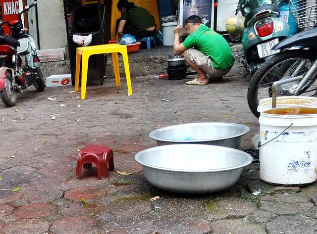 Một quán bún trên phố Hàm Nghi khá nhếch nhác, việc rửa bát đĩa và chế biến thực phẩm ngay tại vỉa hè.