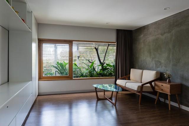 Nhà nằm ở mặt đường nhiều xe cộ đi lại. Để tránh tiếng ồn và bụi, các kiến trúc sư dùng giải pháp lam gỗ mặt tiền, phía sau là lớp cây xanh, vừa tạo thẩm mỹ vừa làm lớp che nắng nhưng vẫn thông thoáng bên trong.