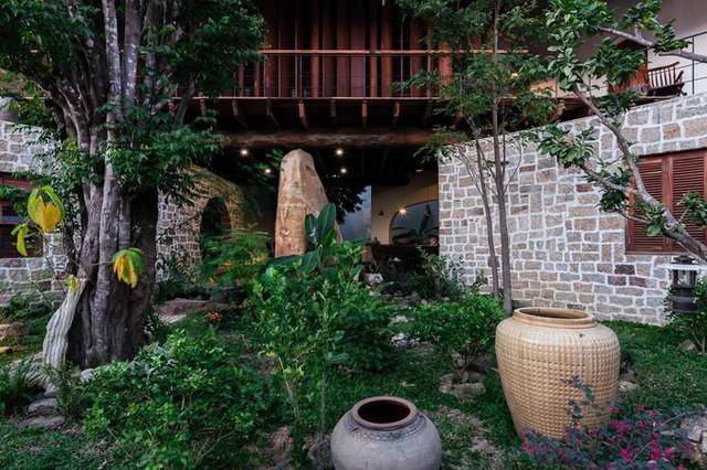 Một hệ thống sân vườn với nhiều cây xanh cao thấp cùng những viên đá nhiều kích cỡ giúp ngôi nhà trở thành một thế giới xanh mát và bình yên.
