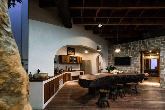 Phòng ăn và bếp liên thông nơi tầng một, nối với nhau bằng một khung cửa vòm.