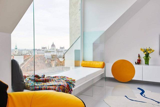 Một ghế dựa lớn được đặt ngay cạnh một cửa kính cũng lớn không kém để ngắm cảnh thành phố.