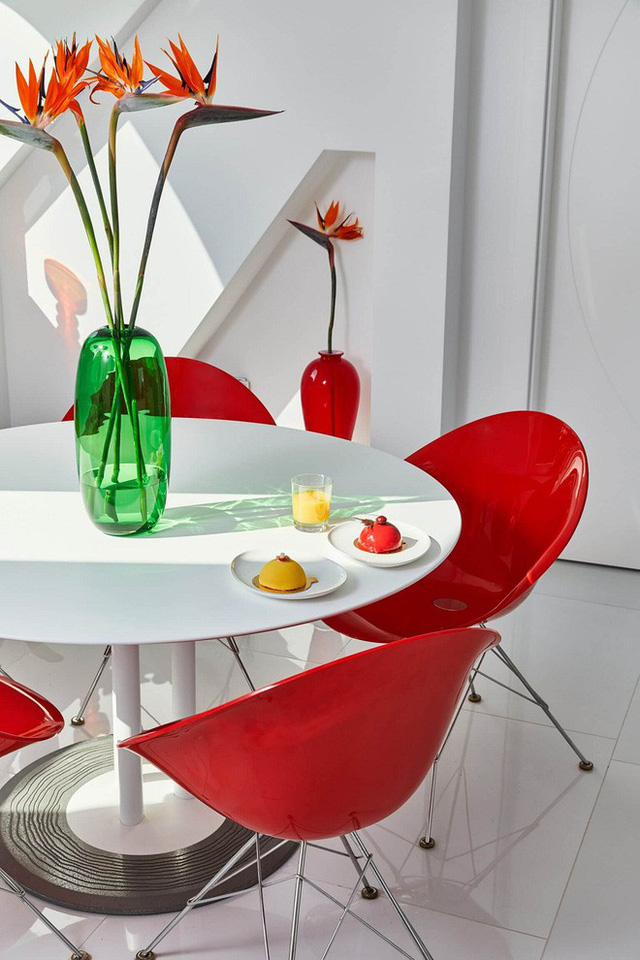 Chiếc bàn thưởng trà với điểm nhấn từ những chiếc ghế có màu đỏ đô nổi bật.