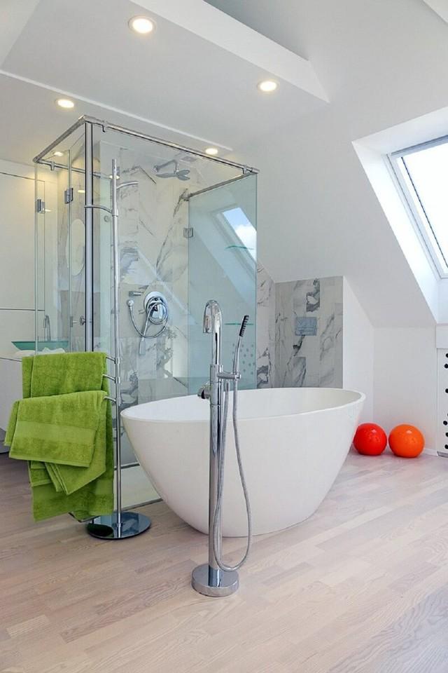 Nhà tắm cũng được thiết kế khá đơn giản với một bồn tắm cỡ vừa và một nhà tắm trong suốt. Một chút gạch hoa được lát tầng thấp để tạo sự khác biệt.