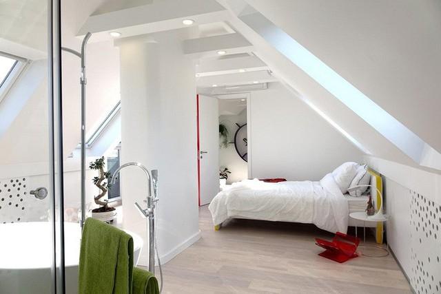 Phòng ngủ nằm ngay bên cạnh nhà tắm, với một giường ngủ nhỏ màu trắng, đầu và đuôi giường được sơn màu vàng đậm làm điểm nhấn.