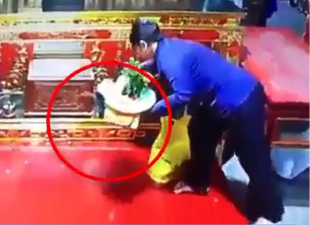 Quái nữ nhanh tay cuỗm túi xách trong chùa. Ảnh cắt từ clip