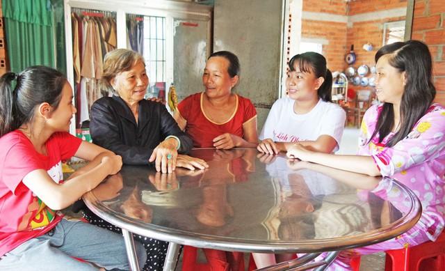 Bà Nguyễn Thị Theo (ngồi giữa) tích cực đến nhà các hộ dân vận động, tuyên truyền. Ảnh: cát Tường