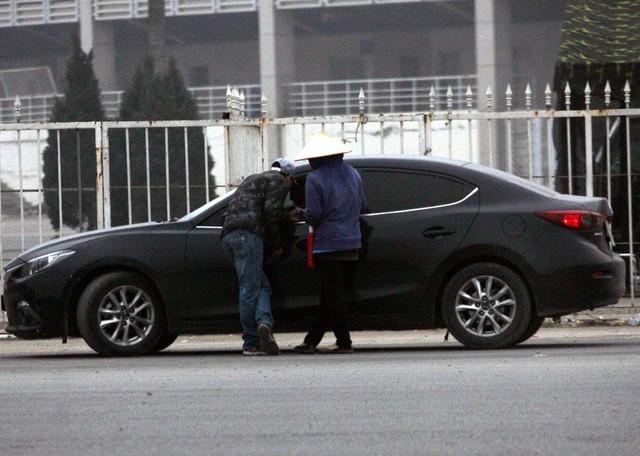 Một chiếc xe ô tô đỗ lại, lập tức đội quân cò vé ập tới.