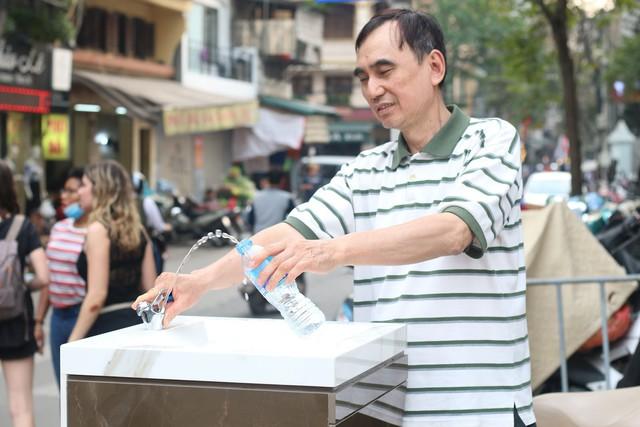 """Anh Hoàng Hồng Hà, tiểu thương tại chợ Hàng Da chia sẻ: """"Những trụ nước thật sự thiết thực cho người dân, đặc biệt là những người lao động buôn bán như chúng tôi. Từ hôm có trụ nước này, ngày nào tôi cũng ra lấy vài bình để uống, mà không phải mua nước như ngày trước nữa"""". Ảnh: Thu Phương"""