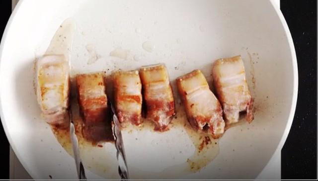 Xếp thịt bạn vừa áp chảo thành vòng quanh đáy nồi cơm, để lại phần giữa nồi không có thịt. Sau khi xếp hết thịt vào thì bạn lấy 1 cốc chịu nhiệt có kích cỡ vừa đủ, đặt vào giữa nồi, cho 2 quả trứng vào. Rải hành, gừng và rót nước lọc vào phần thịt, bật nút Cook và nấu trong khoảng 1 giờ.