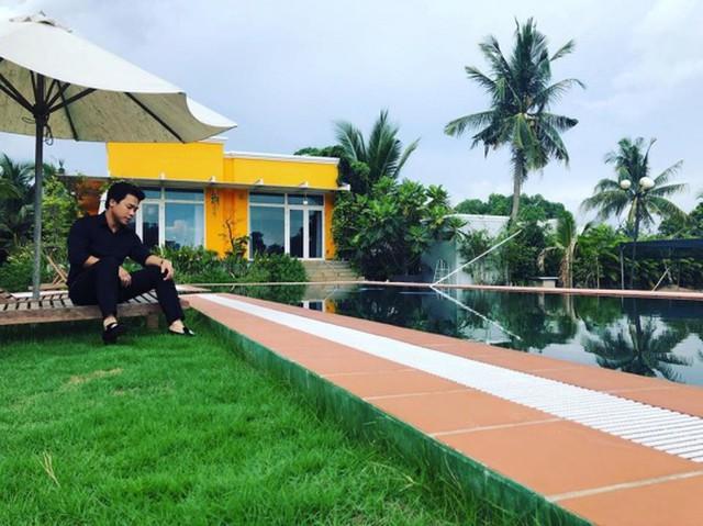 Căn biệt thự được sơn vàng cam nổi bật giữa khu đất đầy cây cối. Một góc biệt thự có hồ bơi xanh mát, sân còn được trải thảm cỏ và có ghế ngồi để nghỉ ngơi, thư giãn.