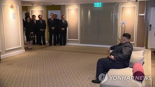 Hình ảnh cắt ra từ phim cho thấy các quan chức đang đứng lắng nghe ông Kim tại khách sạn ở Hà Nội. Ảnh: Yonhap.