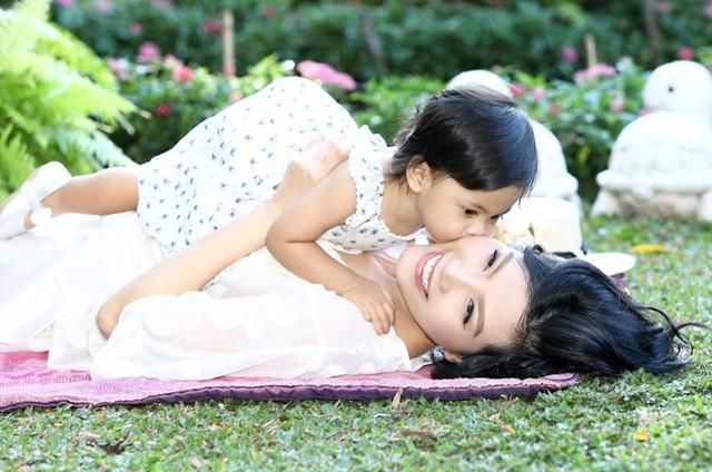 Bé Vi Anh tình cảm hôn má mẹ. Vũ Cẩm Nhung tiết lộ con gái rất quấn mẹ trong khi cậu anh gần gũi bố nhiều hơn.