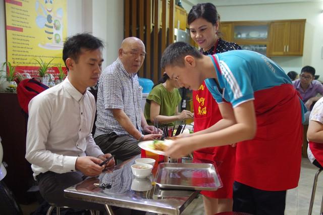 """Chị Nguyễn Thị Lệ Thủy – người quản lí """"Quán Ong Mật"""" hướng dẫn tỉ mỉ những trẻ mắc chứng tự kỷ từ những công việc nhỏ nhất như chào hỏi, cách bưng bê, đặt đồ cho khách."""