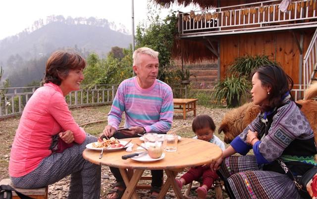 Chị Lỳ đang trao đổi về những hoa văn thêu trên áo với các vị khách nước ngoài.