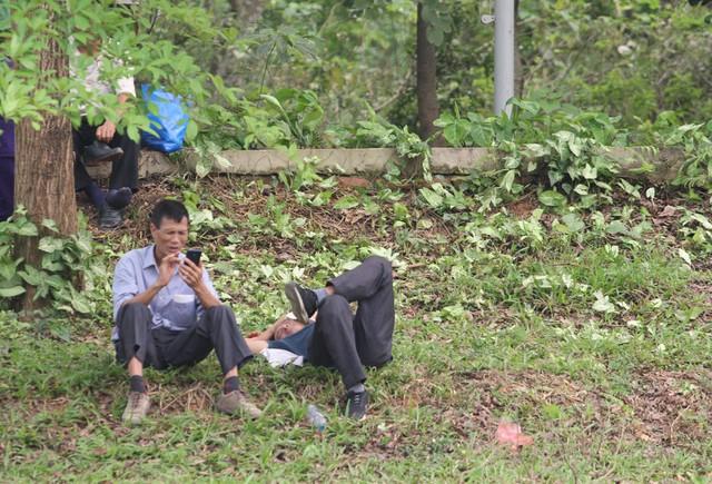 Trước tình cảnh trên, người dân đã phải tá túc vào bãi cỏ, nơi có bóng mát để đặt lưng nghỉ ngơi, ngủ.