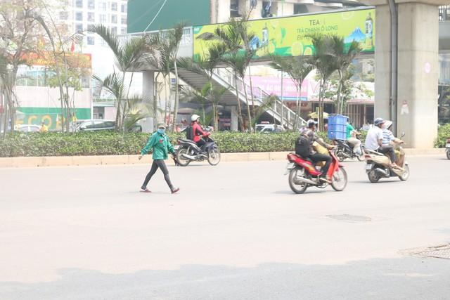 Tuyến đường Nguyễn Trãi, người phụ nữ băng thẳng qua đường mặc nguy hiểm. Trong khi, cách đó không xa có cầu bộ hành cho người đi bộ qua đường.