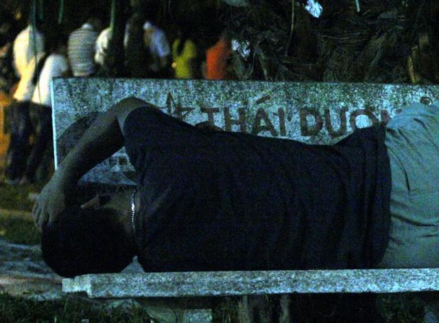 Một nam thanh niên nhanh chân xí chiếc ghế đá tại khu vực Đền Giếng ngủ ngon lành.
