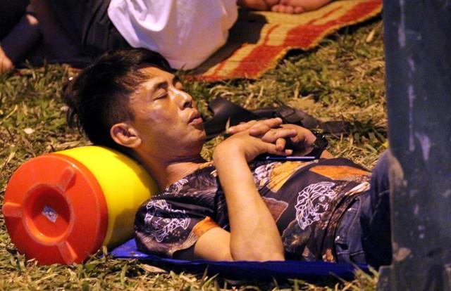 Một nam thanh niên dùng chiếc bình nhựa làm gối tại bãi cỏ dọc quảng trường.