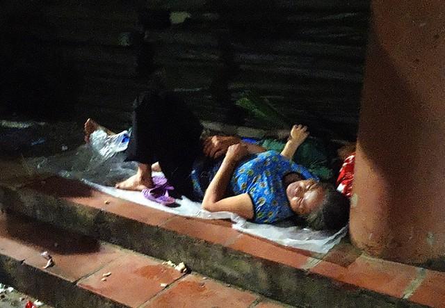 Một người phụ nữ dân tộc trải mảnh nilon mang theo ngủ ngon tại khu vực bậc thềm.