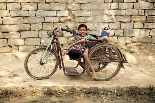 Cặp song sinh trên chiếc xe đạp được chế thêm để tiện cho việc vận động, đi lại. Ảnh: Barcroft.