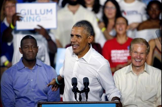 Ngoài diễn thuyết và bán sách, nhà Obama còn tham gia quảng cáo và sở hữu bất động sản đồ sộ. Gia đình Obama sống trong biệt thự rộng 760 m2 với 9 phòng ngủ, lần cuối được rao bán với giá 5,3 triệu USD. Căn biệt thự nằm trong khu Kalorama sầm uất, nơi ái nữ của tổng thống đương nhiệm - Ivanka Trump cũng sở hữu một căn nhà. Trong ảnh, ứng cử viên Thống đốc bang Florida, Andrew Gillum, (trái) và Thượng nghị sĩ Bill Nelson (phải) lắng nghe ông Obama khi ông đang diễn thuyết bỏ phiếu cho một cuộc mít tinh tại Miami. Ảnh: Getty Images.