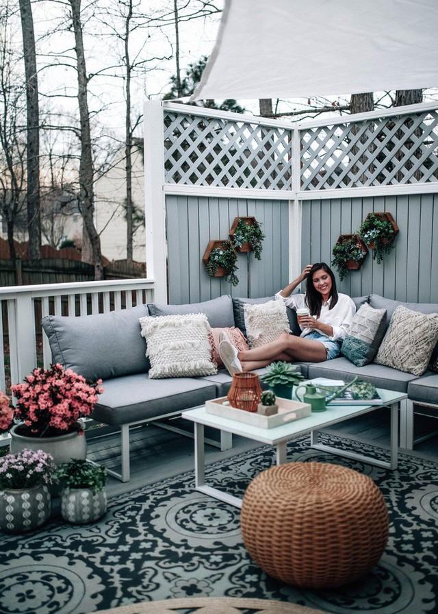 Sàn boho màu xám với những điểm nhấn của hoa màu xanh lá cây và màu hồng tự nhiên cộng với một chiếc ghế dài bằng liễu gai.