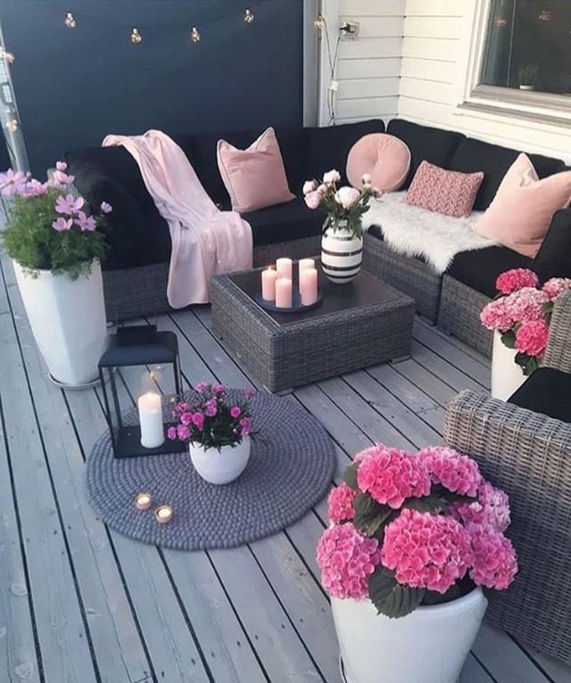 Sàn màu đen và đỏ với đồ nội thất đan lát, gối màu đỏ và những chậu hoa màu hồng nóng bỏng.