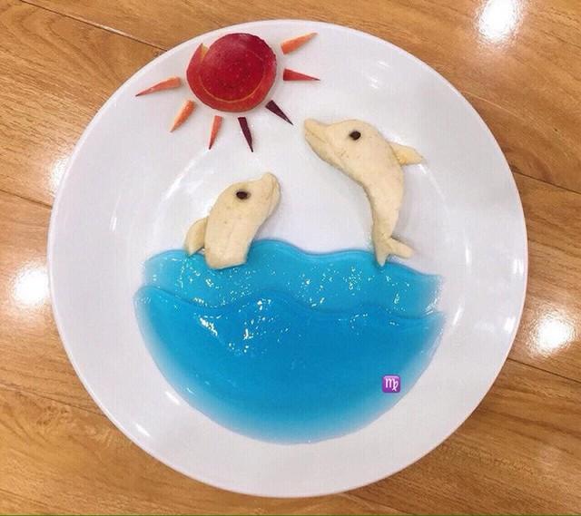 Hết cơm, món ăn sáng lại đến món ăn vặt với thạch rau câu, chuối và táo được tạo hình biển xanh trong vắt với 2 chú cá heo nô đùa dưới nắng.