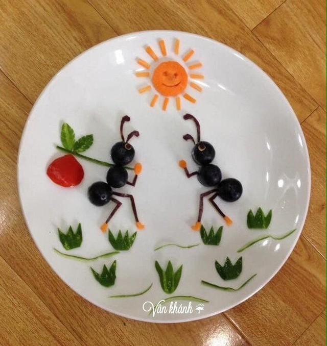 2 chú kiến đang chuyện trò vui vẻ được tạo thành từ nho, dưa leo, táo và cà rốt.