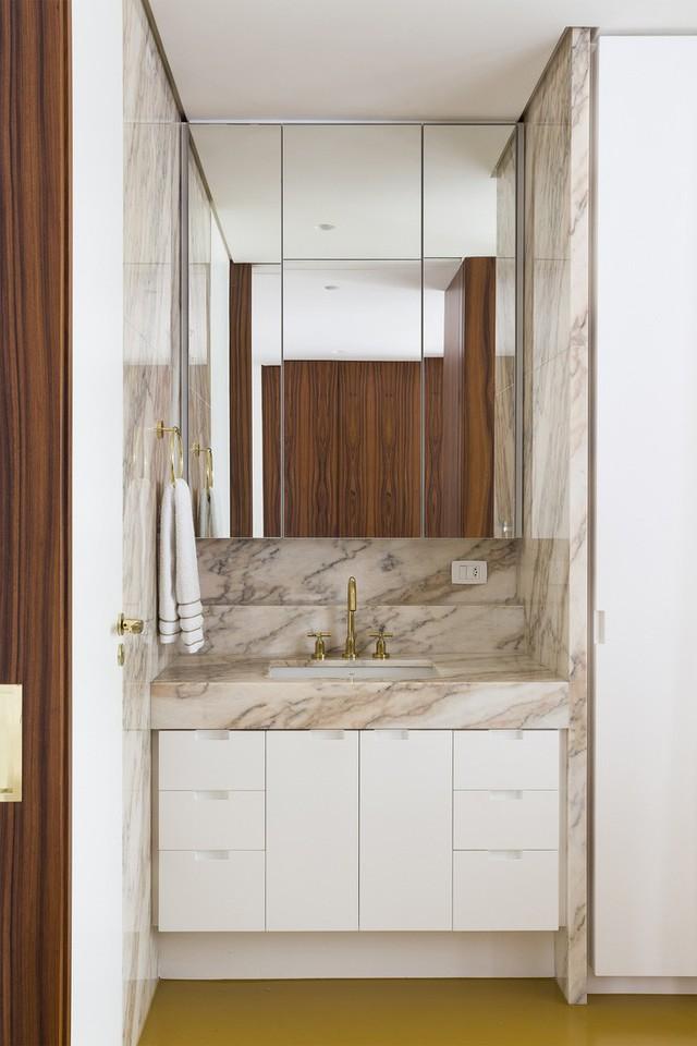 Phòng tắm nhỏ nhưng thanh lịch, nổi bật với bề mặt đá cẩm thạch và gương.