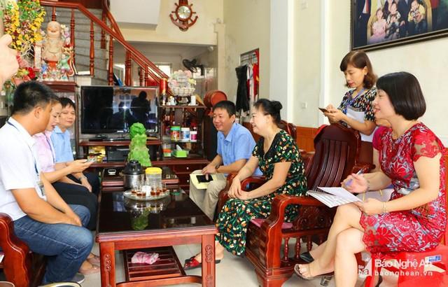 Các điều tra viên cập nhật thông tin ngay trên phần mềm của điện thoại thông minh tại một hộ dân ở TP Vinh (Nghệ An). Ảnh: Nguyễn Hải