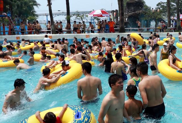 Tại khu vực bể tạo sóng, hàng trăm người dân thích thú vui đùa, nhảy nước, tắm mát.