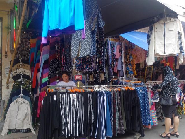 Một quầy hàng thời trang chống nắng phủ kín lối đi tại chợ Nhà Xanh. Ảnh: Bảo Loan