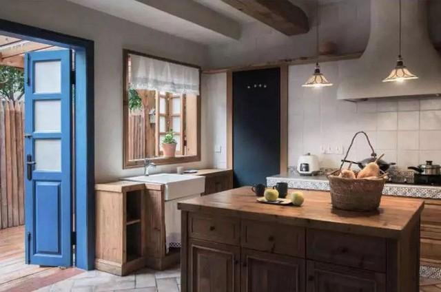 Góc nhỏ nấu nướng có cửa thông ra vườn. Đảo bếp cũng được tận dụng từ gỗ cũ sưu tầm được từ các vùng lân cận để tạo sự thân thiện và hài hòa với không gian chức năng.