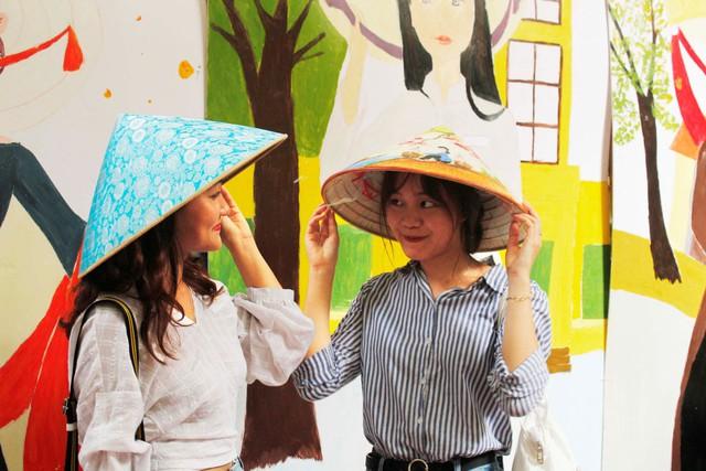 Các bạn trẻ hào hứng đội những chiếc nón lá làng Chuông.
