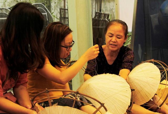 Không chỉ tham quan triển lãm, những người đến tham dự còn đích thân trải nghiệm làm nón lá dưới sự hướng dẫn tận tình của những nghệ nhân làng Chuông.