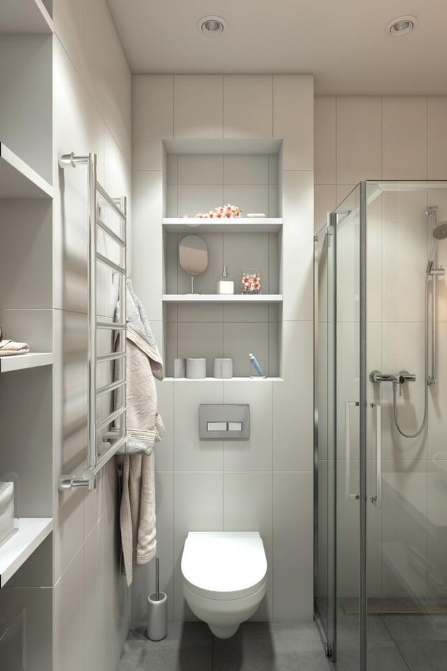 Phòng tắm được bố trí ở phía bên trái ngay bên cạnh vị trí cửa ra vào. Một phòng tắm rất hẹp nhưng không chật chội, trái lại được thiết kế cực kỳ thông minh với buồng tắm đứng cửa gương trong suốt cùng những chiếc hộc lưu trữ tận dụng bề mặt bức tường một cách hiệu quả. Nhờ vậy mà các vật dụng được sắp xếp ngăn nắp, thậm chí còn có không gian cho lọ hoa hay đèn thả trang trí đẹp mắt.