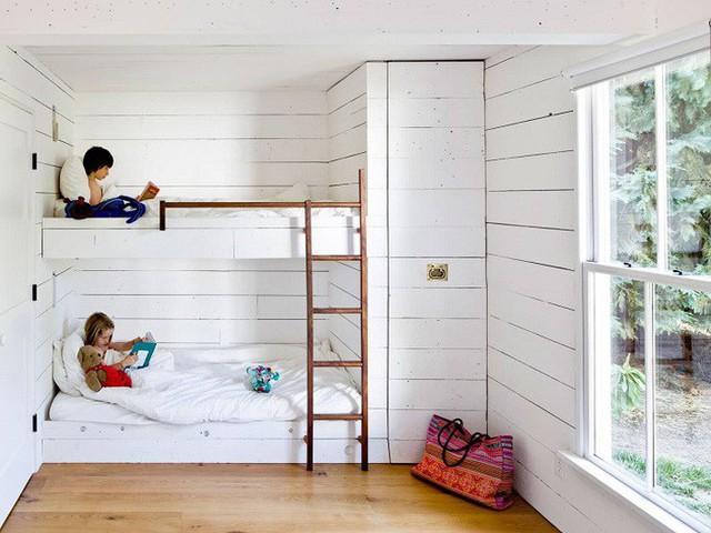 Phòng ngủ của 1 bé gái và bé trai với các kệ đựng đồ dùng và cầu thang gỗ lên xuống.