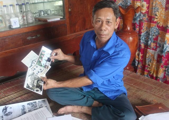 Ông Nguyễn Duy Đông nâng niu những tấm hình lịch sử.