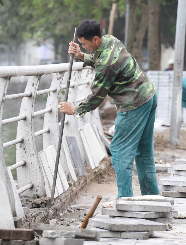Công nhân dùng xà beng xén mép cho vừa với viên gạch.