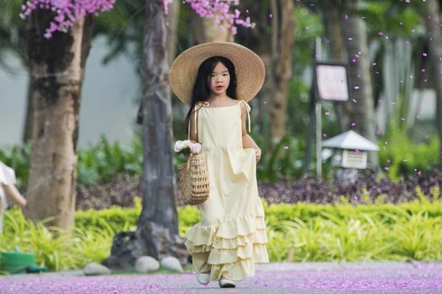Cô bé diện một chiếc váy duyên dáng, kết hợp nón vá túi cói tạo điểm nhấn.