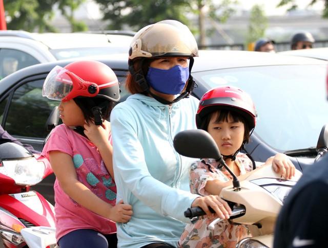 Một bà mẹ chở 2 cô con gái bằng xe máy di chuyển từ hướng Ngọc Hồi lên Giải Phóng.