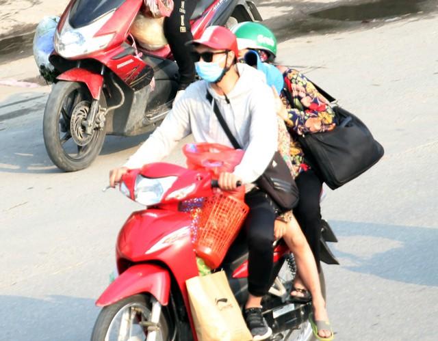 Một gia đình trẻ chở nhau trên xe máy với lỉnh kỉnh đồ đạc từ quê lên.