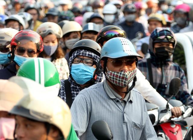 Người dân di chuyển bằng xe máy với quãng đường dài nên đã phải trang bị khẩu trang, mũ, kính, áo chống nắng.