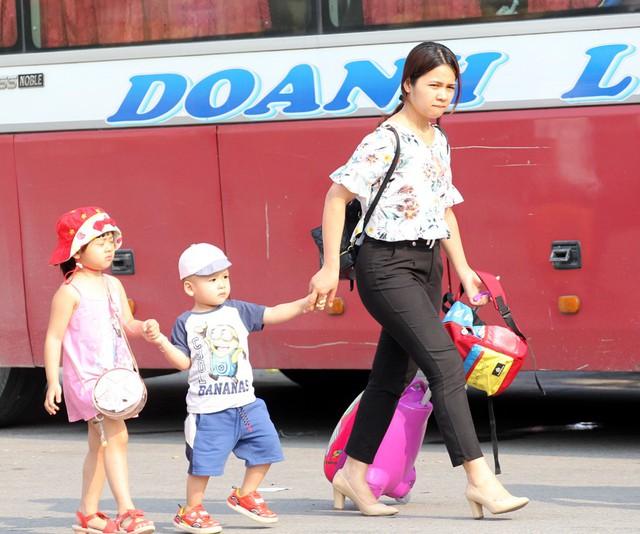 Một bà mẹ dẫn theo 2 con nhỏ nhanh chân ra khu vực đón chờ taxi.
